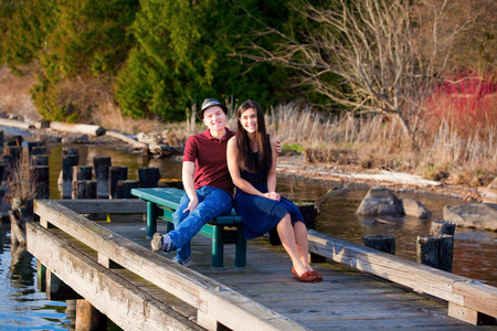 Happy young interracial couple sitting together on dock over lake photo