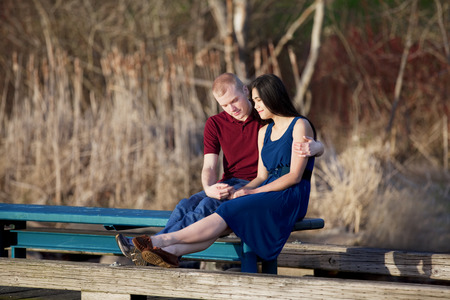 Young interracial couple quietly praying together on wooden pier over water photo
