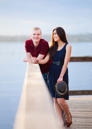 Young happy interracial couple standing together on wooden pier overlooking lake photo