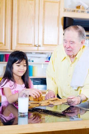 pan asian: Elderly man sharing cookies with granddaughter Stock Photo