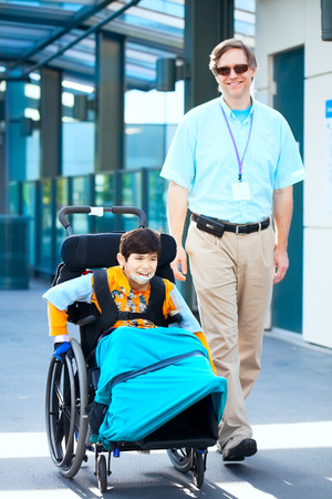 cerebral palsy: Man walking next to little boy in wheelchair outside medical facility