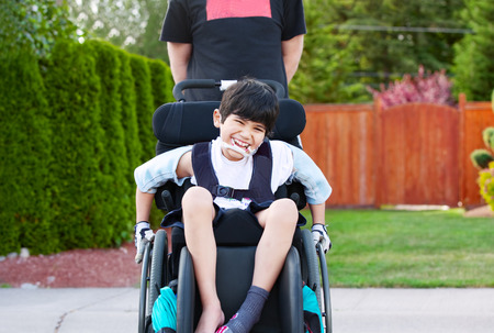 needs: Happy little disabled boy wheeling around outdoors in wheelchair Stock Photo