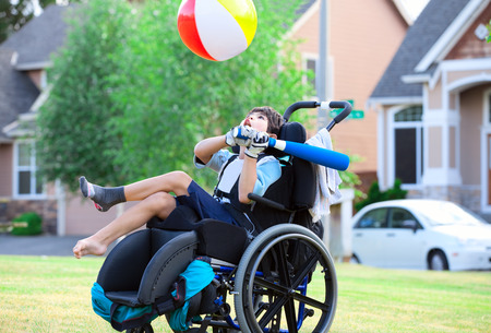 handicapped person: Disabled little boy playing ball in the park