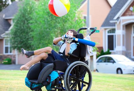 persona en silla de ruedas: Niño con discapacidad jugando pelota en el parque