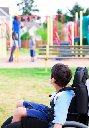 Disabled little boy in wheelchair sadly watching children play on playground photo