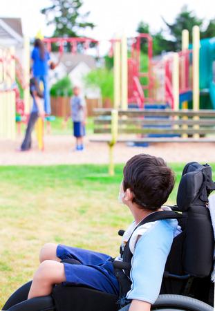 dětské hřiště: Zakázáno malý chlapec na vozíku smutně pozoroval děti hrají na hřišti