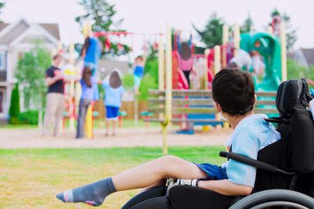 Gehandicapte jongetje in rolstoel helaas kijken naar de kinderen spelen op de speelplaats