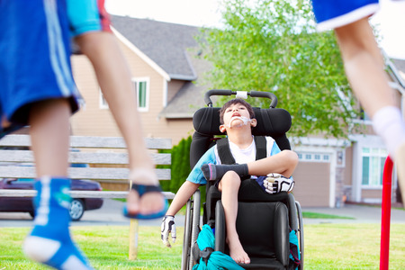 ostracized: Handsome disabled child in wheelchair watching children play at park