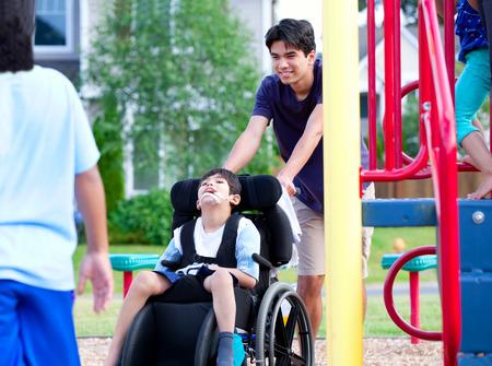 persona en silla de ruedas: Muchacho lisiado en silla de ruedas que goza amigos viendo jugar al parque el gimnasio de la selva
