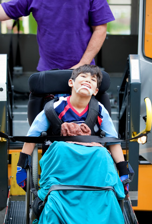 schoolbus: Happy disabled seven year old boy being transported on handicap school bus lift