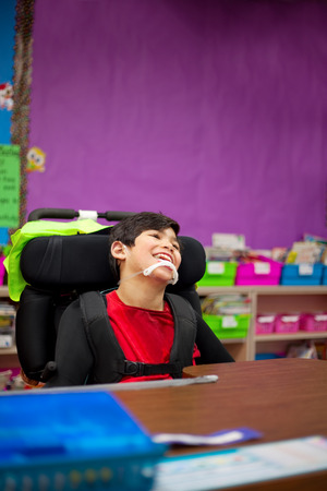 onderwijs: Disabled seven year old boy sitting at desk in classroom