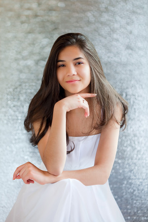 girl sit: Beautiful biracial teen girl in white dress sitting, thinking towards camera