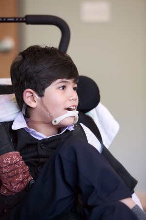 cerebral palsy: Handsome disabled eight year old biracial boy smiling and relaxing in wheelchair