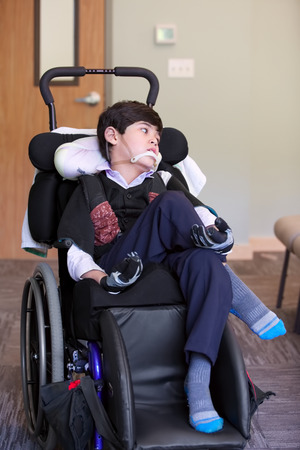 eight year old: Handsome disabled eight year old biracial boy smiling and relaxing in wheelchair