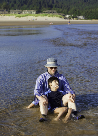 cerebral palsy: Caucasian father playing in water on beach with disabled son