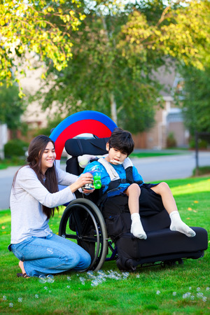cerebral palsy: Biracial older sister playing outdoors with disabled little brother in wheelchair Stock Photo