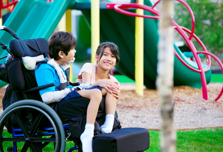 special needs: Sister sitting next to disabled brother in wheelchair at playground Stock Photo
