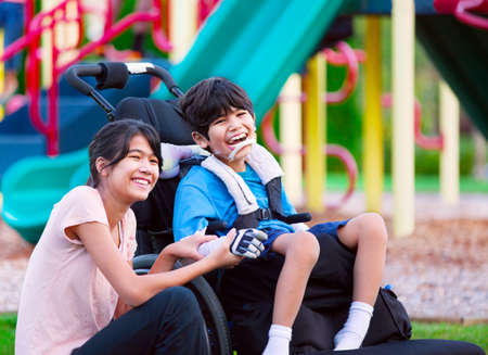 cerebral palsy: Sister sitting next to disabled brother in wheelchair at playground Stock Photo