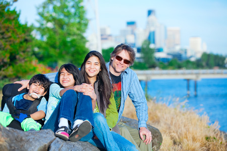 cerebral palsy: Disabled boy in wheelchair with family outdoors on sunny day, with city skyline in background