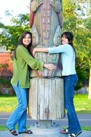 the totem pole: Two young, biracial teen girl in park hugging a totem pole on sunny day
