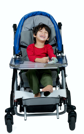 three year old: Three year old biracial disabled boy in medical stroller, happy and smiling