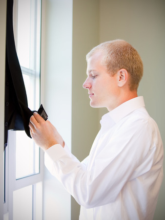 'getting ready': Caucasian groom checking his jacket, getting ready for his wedding