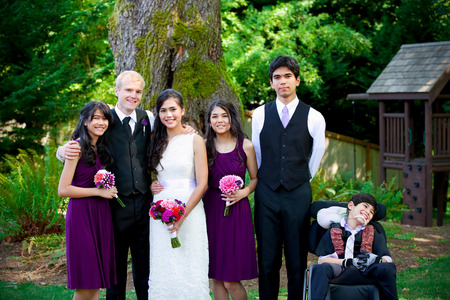 cerebral palsy: Interracial wedding. Groom standing with his biracial brides brothers and sisters outdoors. Youngest boy is disabled with cerebral palsy. Stock Photo