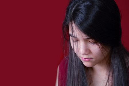thai teen: Beautiful, biracial teen girl looking down, depressed or sad, on red background Stock Photo