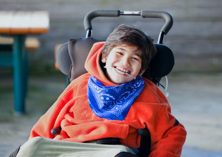 Knap, gelukkig biracial acht jaar oude jongen glimlachend in rolstoel buitenshuis