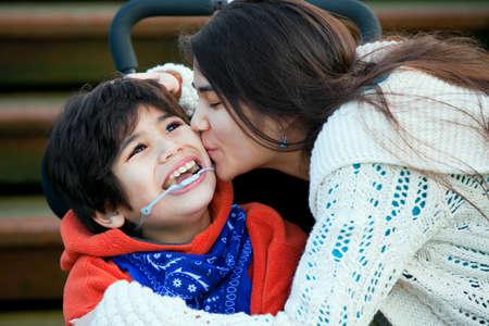 discapacidad: Hermana besando hermano pequeño discapacitado sentado en silla de ruedas en la mejilla Foto de archivo