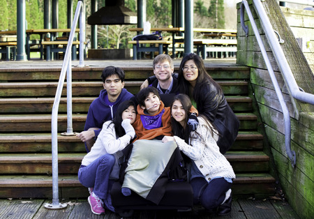 cerebral palsy: Interracial family surrounding disabled boy in wheelchair outdoors by stairs, child has cerebral palsy Stock Photo