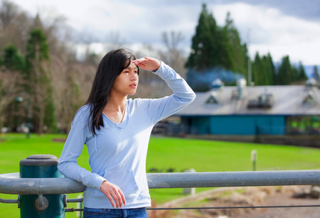 biracial: Young biracial teen girl standing, leaning against railing at park shading eyes to look off to side