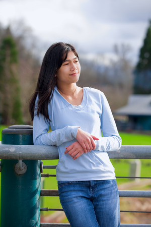 biracial: Young biracial teen girl standing, leaning against railing at park Stock Photo