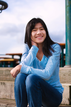 biracial: Young biracial teen girl in blue shirt and jeans sitting on wooden steps outdoors on overcast cloudy day
