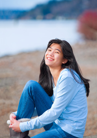 biracial: Young biracial teen girl in blue shirt and jeans sitting along rocky lake shore on bright overcast day outdoors