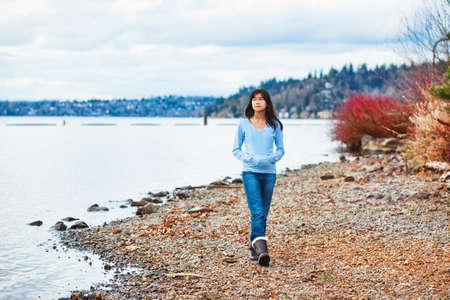 biracial: Young biracial teen girl in blue shirt and jeans walking along rocky shoreline of lake in early spring or fall