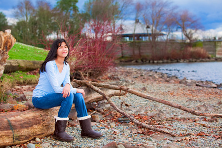 biracial: Young biracial teen girl in blue shirt and jeans sitting on large log on rocky beach by lake
