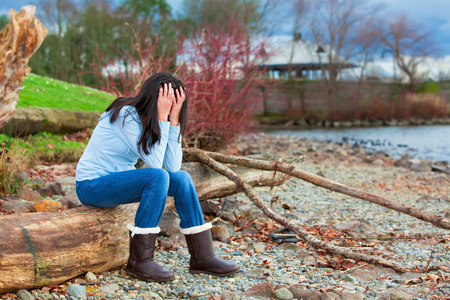 Sad young biracial teen girl in blue shirt and jeans sitting on log along rocky beach by lake Stock Photo