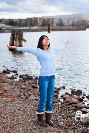 alabando a dios: Chica adolescente birracial joven en camisa azul y pantalones vaqueros, con los brazos levantados y extendidos, alabando a Dios en la costa rocosa por el lago en un d�a nublado