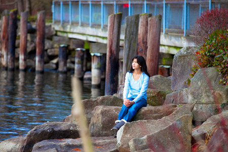 neutrals: Young biracial teen girl in blue shirt and jeans sitting on large boulders along lake shore, looking out over water Stock Photo