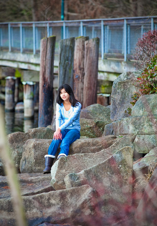 neutrals: Young biracial teen girl in blue shirt and jeans sitting on large boulder along lake shore, relaxing. Earyl autumn or spring season.