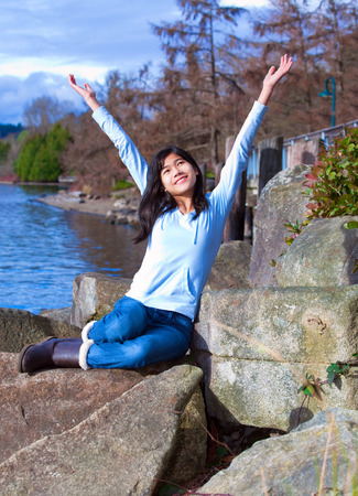 neutrals: Happy young biracial teen in blue shirt and jeans sitting on large rock by lake shore, arms raised in praise.