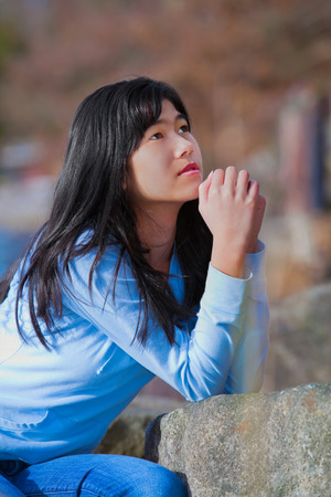 Young biracial teen girl in blue shirt and jeans quietly sitting outdoors leaning on rocks praying