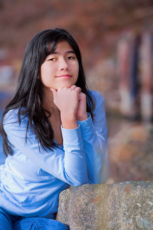 neutrals: Young teen biracial girl in blue shirt and jeans quietly resting elbows on rock along lake shore, sitting  with serious expression