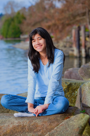 neutrals: Young biracial teen girl in blue shirt and jeans sitting on large boulder or rocks along rocky lake shore, smiling and reclining