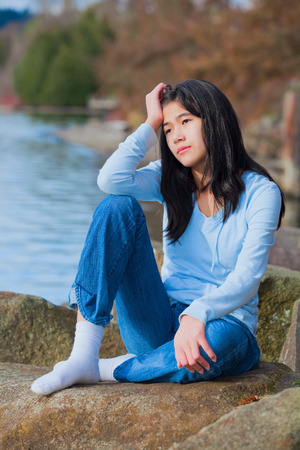 neutrals: Young unhappy biracial teen girl in blue shirt and jeans sitting on rocks along lake shore, looking off to side, resting head in hand and one knee raised.