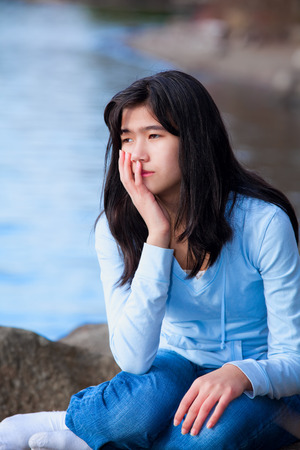 neutrals: Sad biracial teen girl in blue shirt and jeans sitting on rocks along lake shore, lonely expression Stock Photo