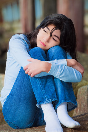 knees bent: Sad biracial teen girl in blue shirt and jeans sitting on rocks along lake shore with knees pulled up to chest, lonely expression