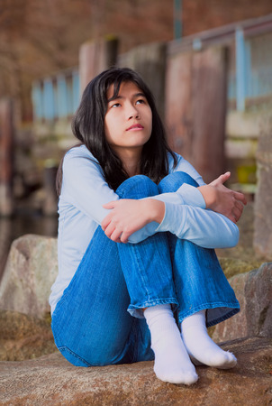 knees bent: Sad biracial teen girl in blue shirt and jeans sitting on rocks along lake shore, lonely expression Stock Photo