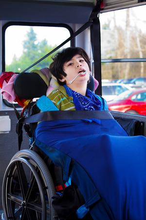 cinturón de seguridad: Birracial minusválidos ocho años de edad, muchacho en silla de ruedas con cinturón de seguridad abrochado en el autobús escolar